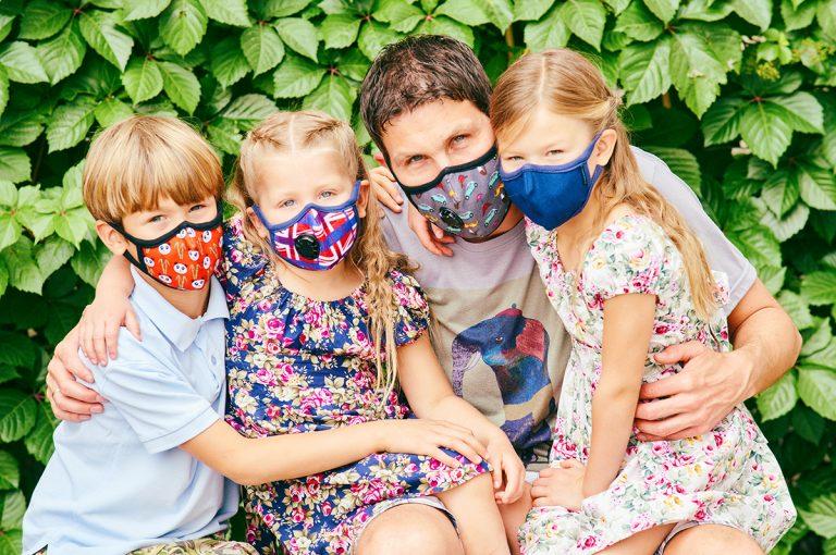 ojciec z dziećmi w maskach gazowych