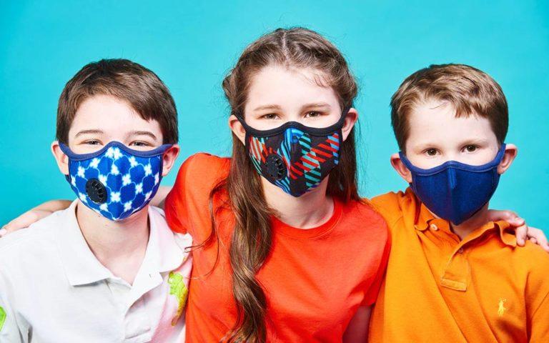 trójka dzieci w maskach antysmogowych